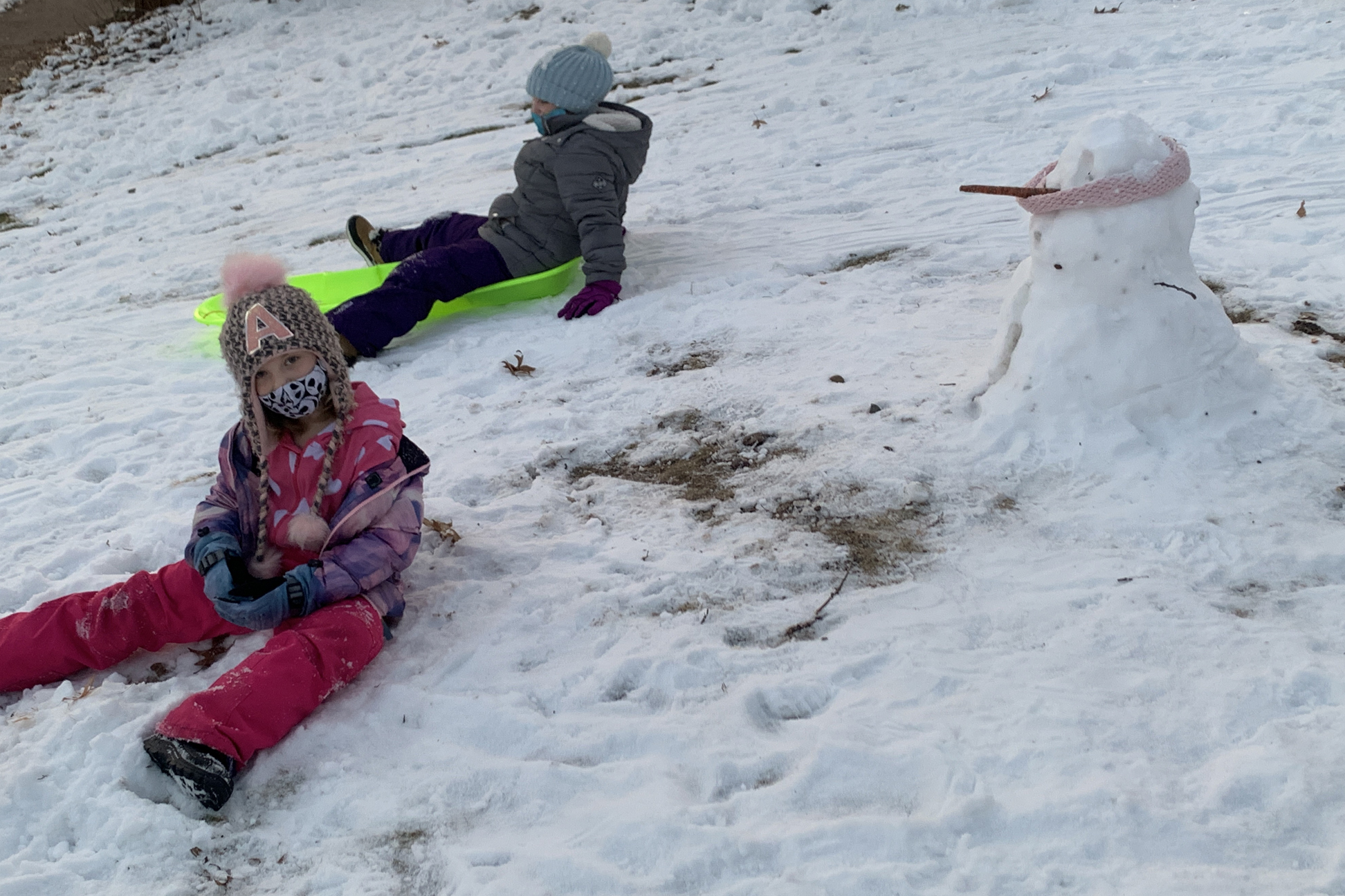 Two children playing in the snow near a snowman.