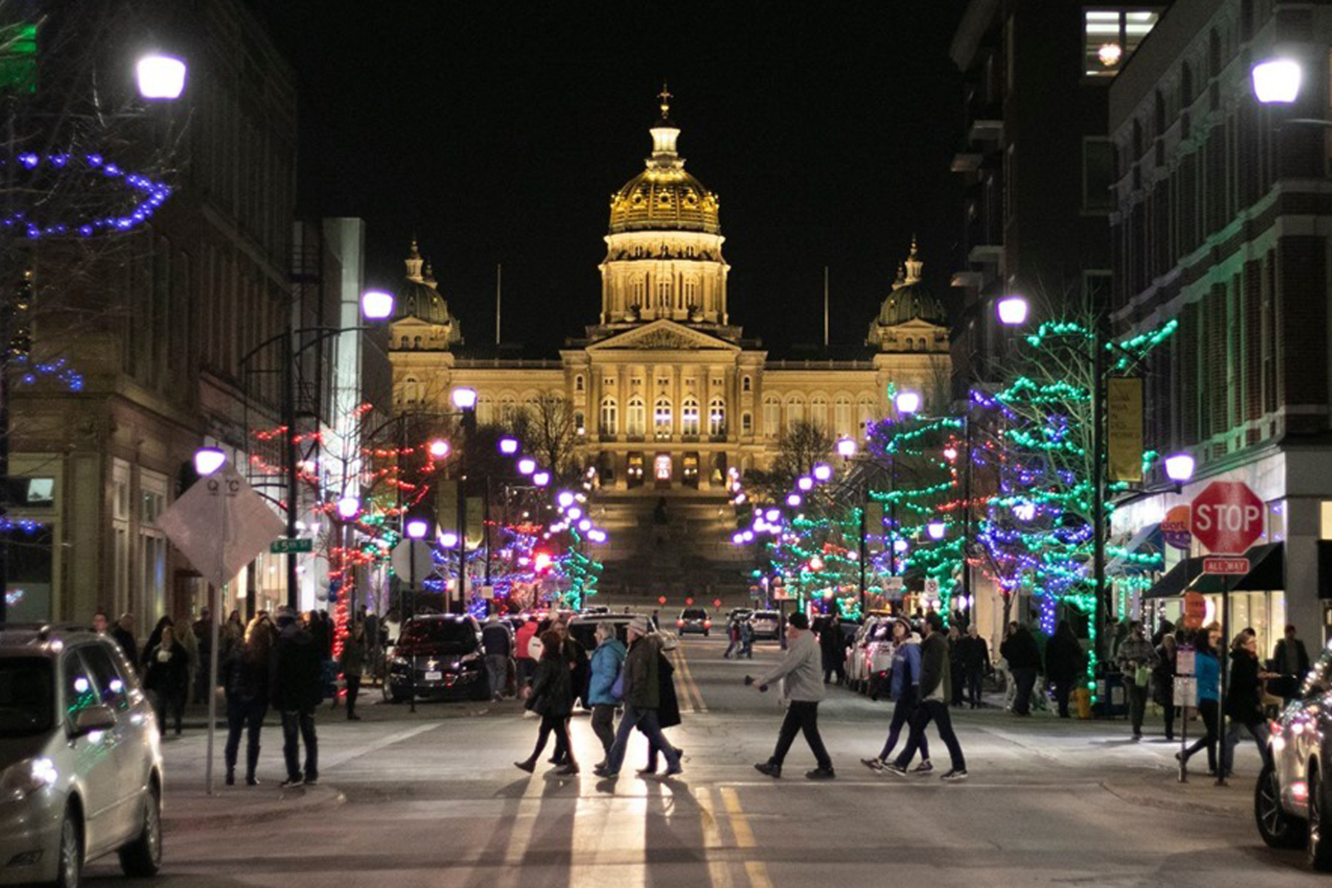 Bustling street with pedestrians, holiday lights and a view of the Iowa Capitol building.