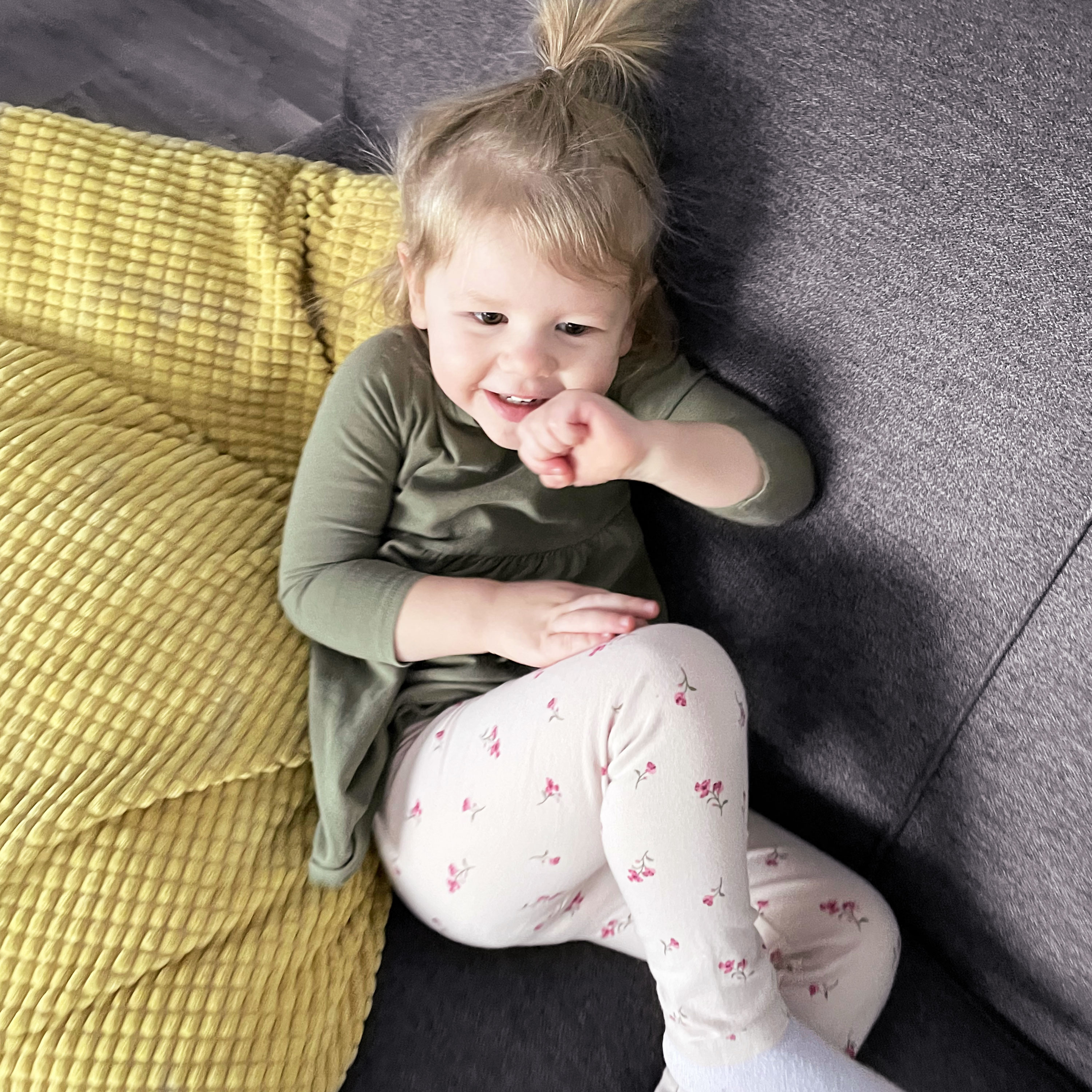 Smiling girl lying on a grey couch with a yellow pillow.