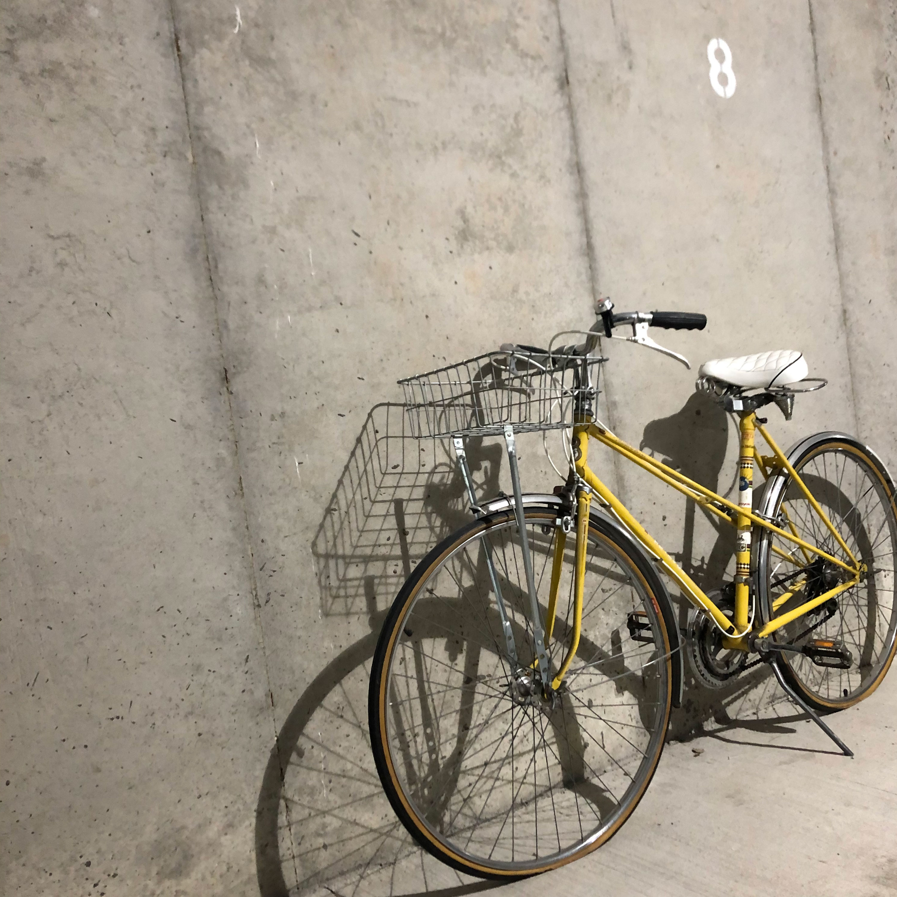 Yellow bike propped up against a grey cement wall.