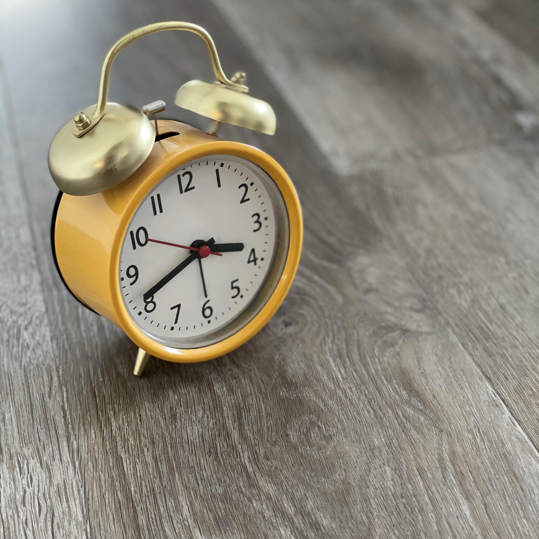 Yellow alarm clock sitting on a grey wood floor.