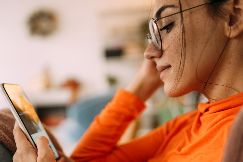 Woman in glasses looking at her cell phone.