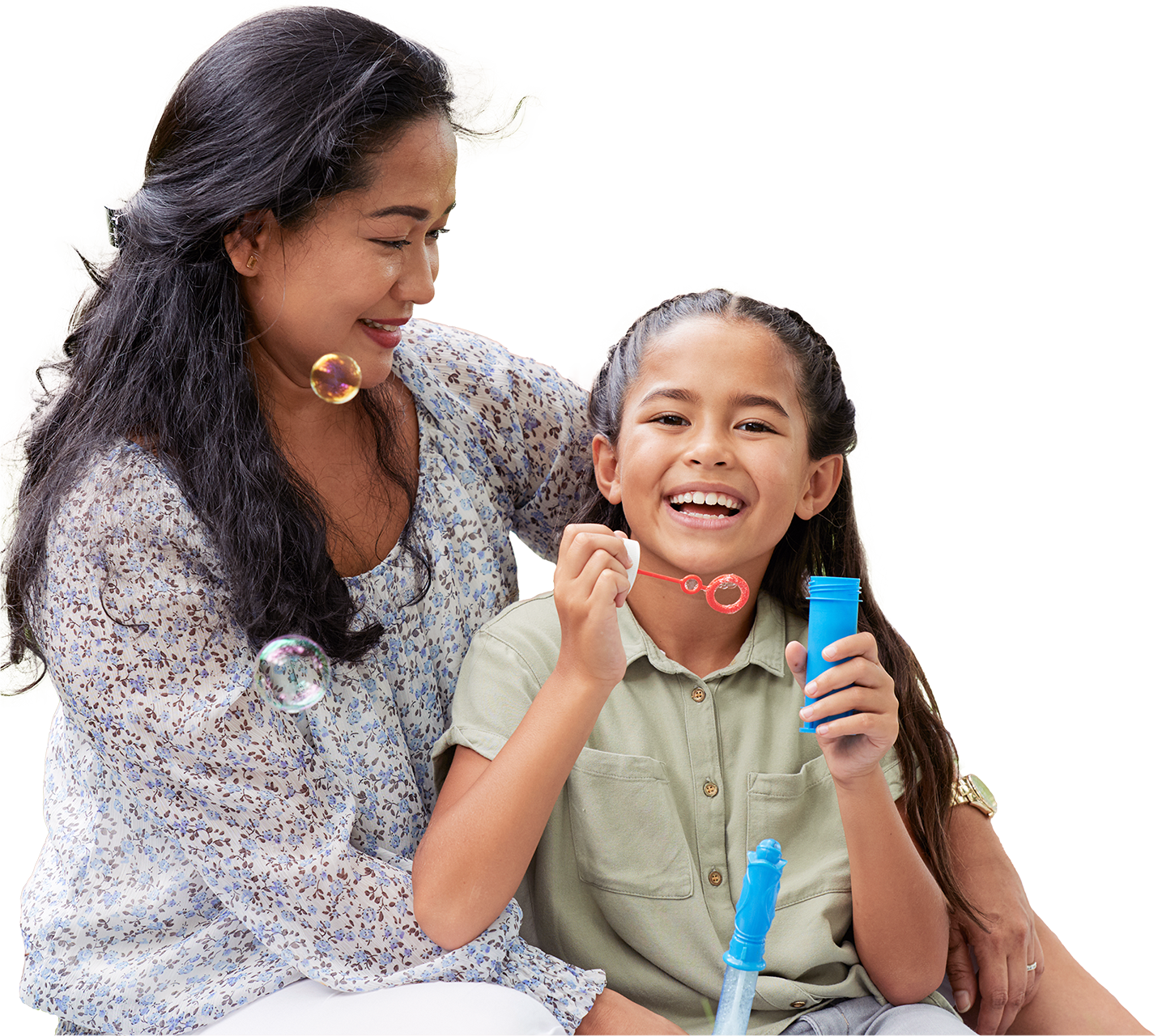 Hispanic mother smiling down and cuddling her smiling daughter who is blowing bubbles