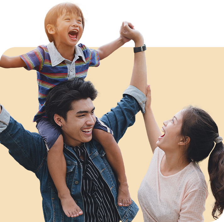 Happy child in rainbow shirt sitting on mans shoulders with woman looking upward at child