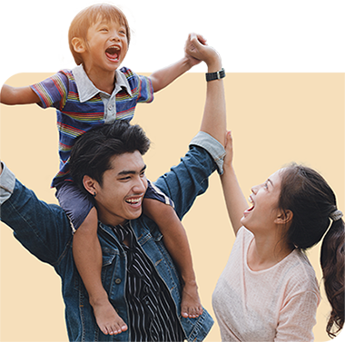 Smiling child in rainbow shirt sitting on mans shoulders with smiling woman looking up at child