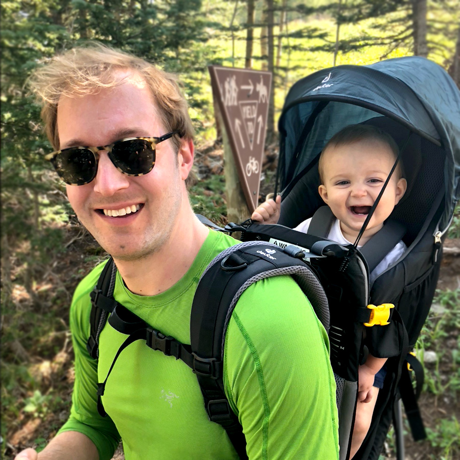 Smiling Jason Bornhorst outside with laughing son in travel back pack
