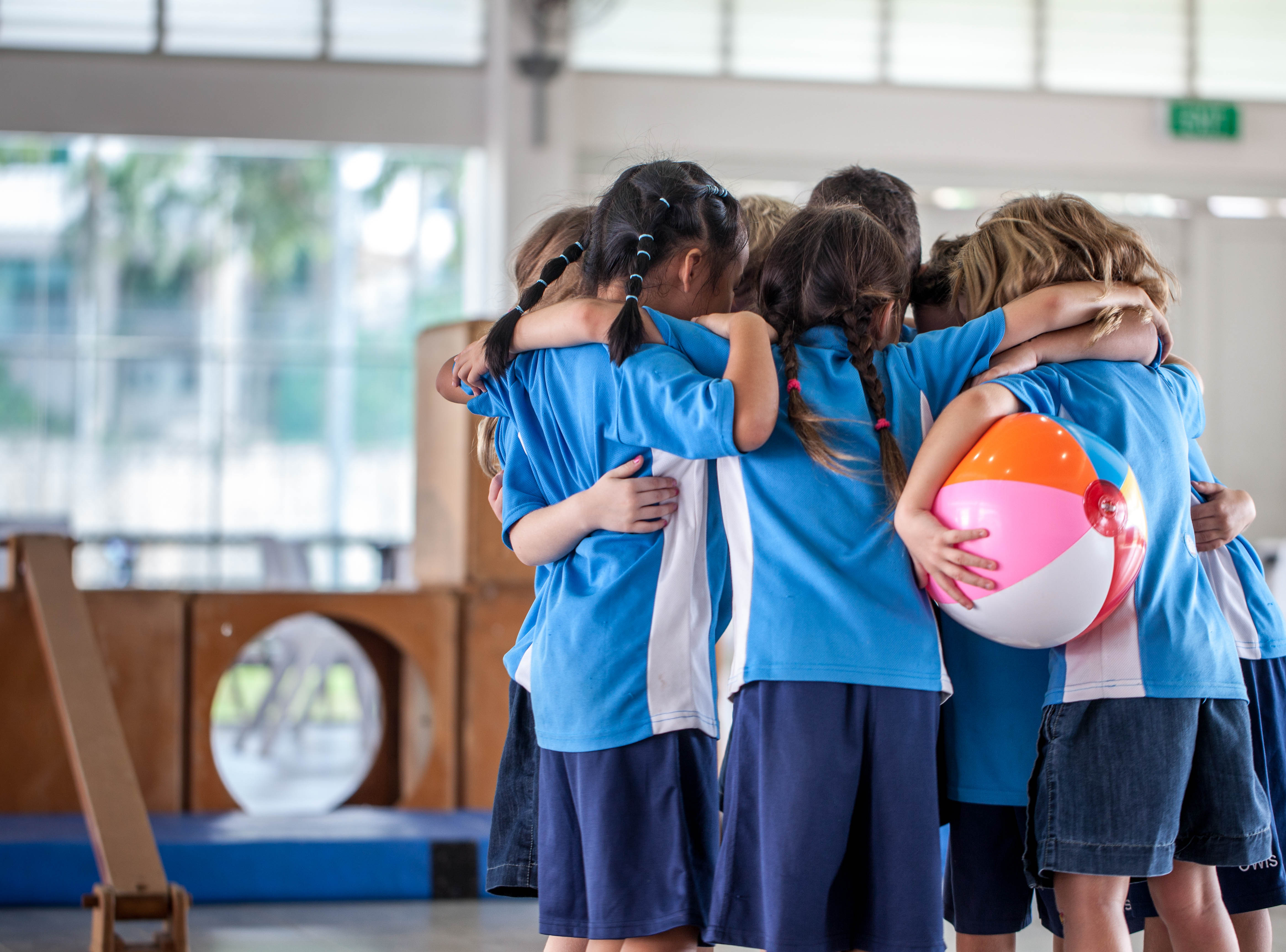 Students-in-a-huddle-with-ball