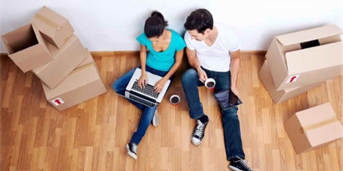 Couple sitting on the floor with moving boxes, looking at a laptop.