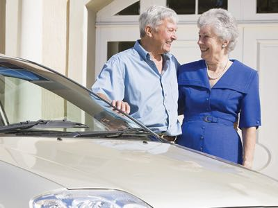 Older couple smiling, standing next to their car