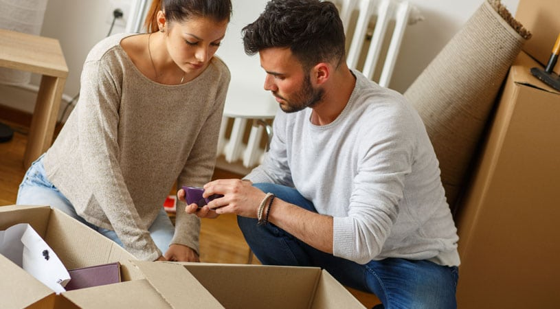 Couple Inspecting Broken Items Damaged By Cheap Removalists