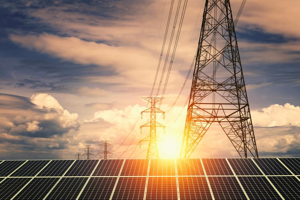 Eine Photovoltaikanlage mit einer Stromleitung, bewöltem Himmel und Sonnenuntergang im Hintergrund