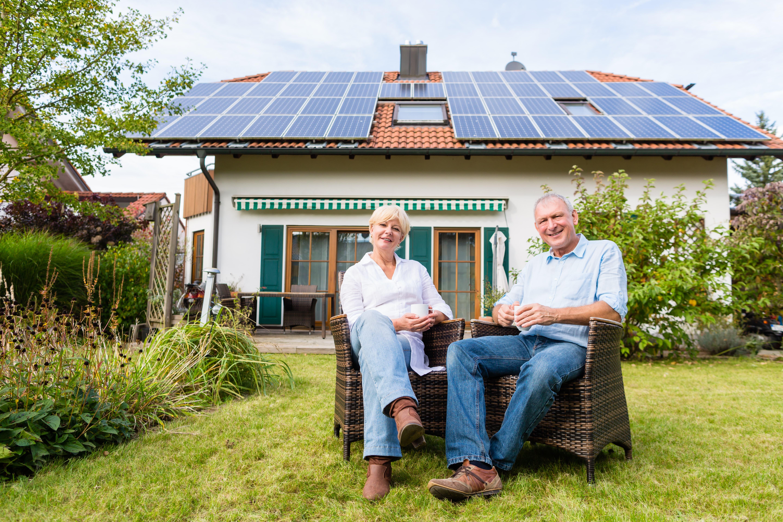 Ein älteres Paar auf Stühlen im Garten mit einem Haus im Hintergrund, das eine Solaranlage auf dem Dach hat