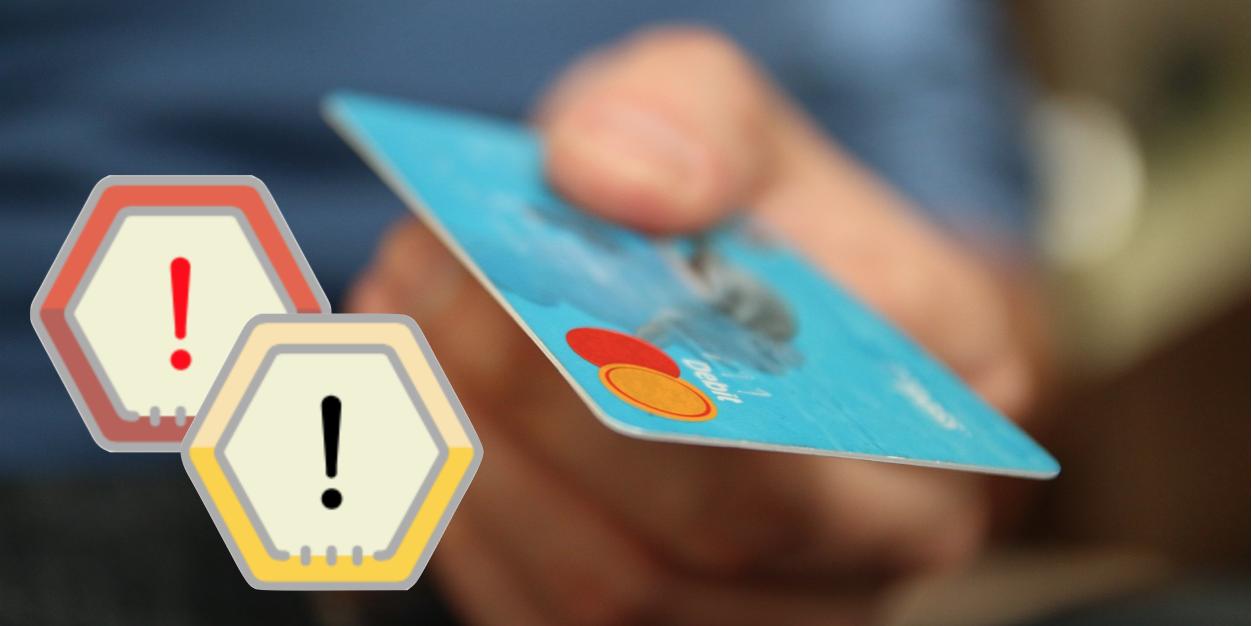 Zwei Warnschilder neben einer Kreditkarte