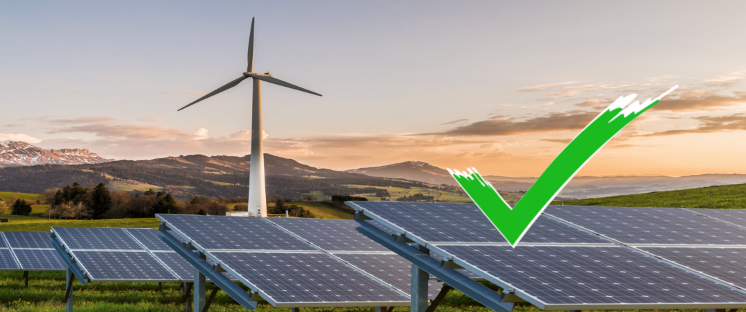 Ein Windkraftrad und Solaranlagen in der Natur mit einem grünen Haken, die unser Grünstrom Fazit symbolisieren