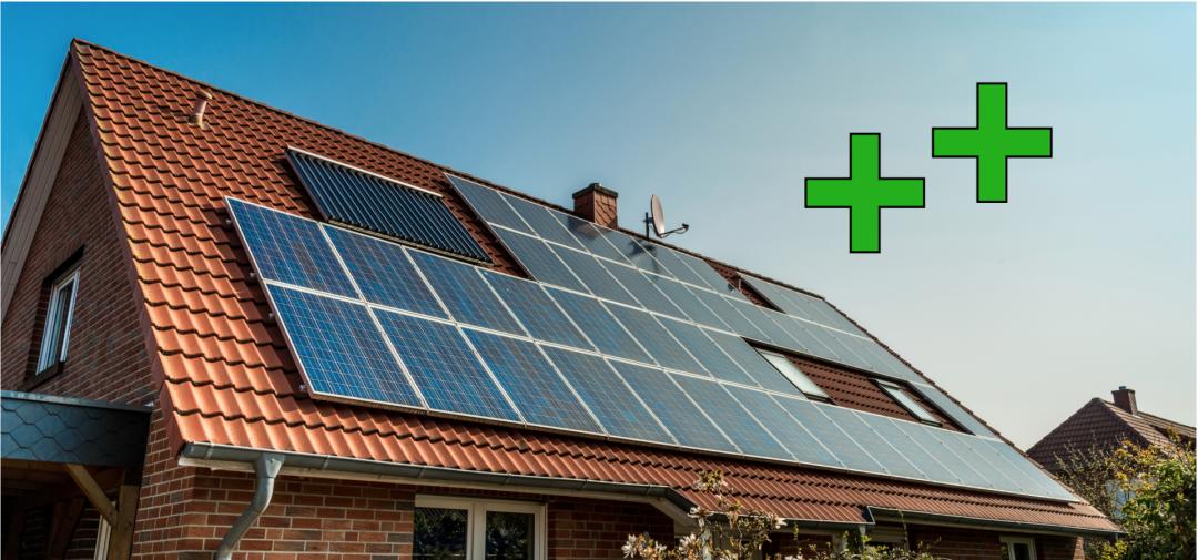 Die Vorteile eine PV-Anlage: zwei grüne Plus Zeichen über einem Solardach mit Photovoltaikanlage