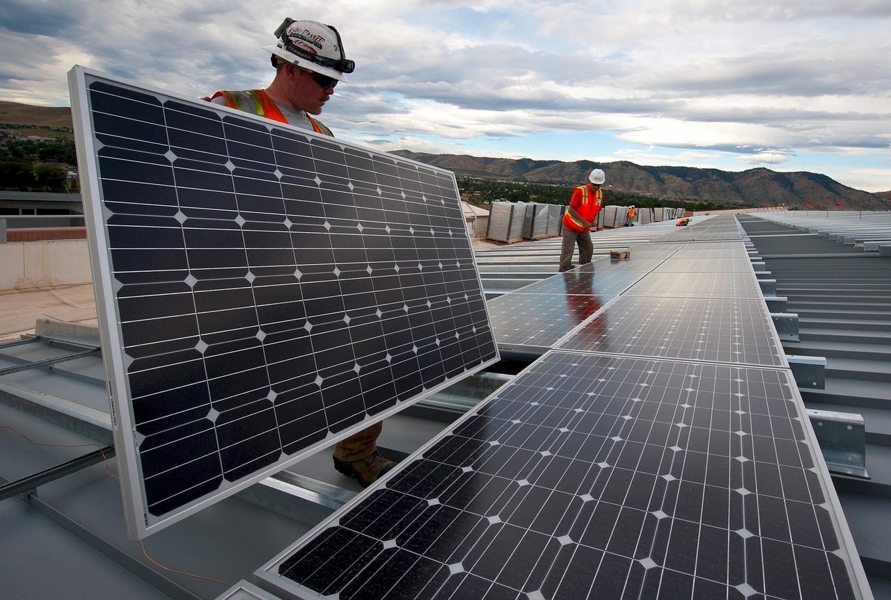 Solaranlage kaufen oder mieten - Arbeiter intallieren Solarmodule auf einem Dach
