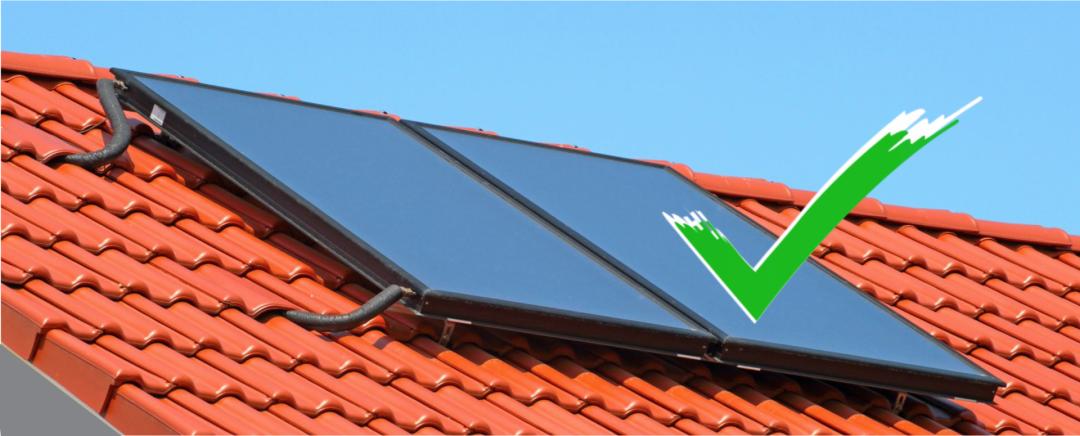 Eine Solarheizung auf einem roten Dach mit grünem Haken, der die Vorteile der Solarheizung symbolisert