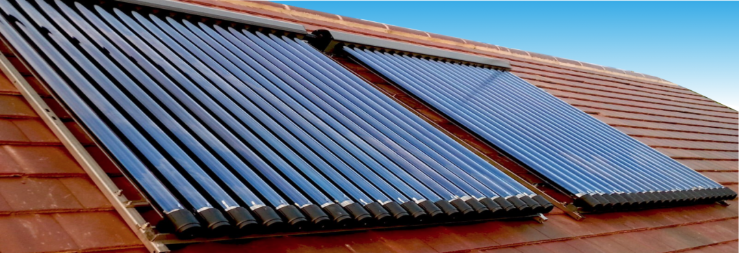 Eine Solarthermie Anlage auf einem roten Dach mit blauem Himmel im Hintergrund
