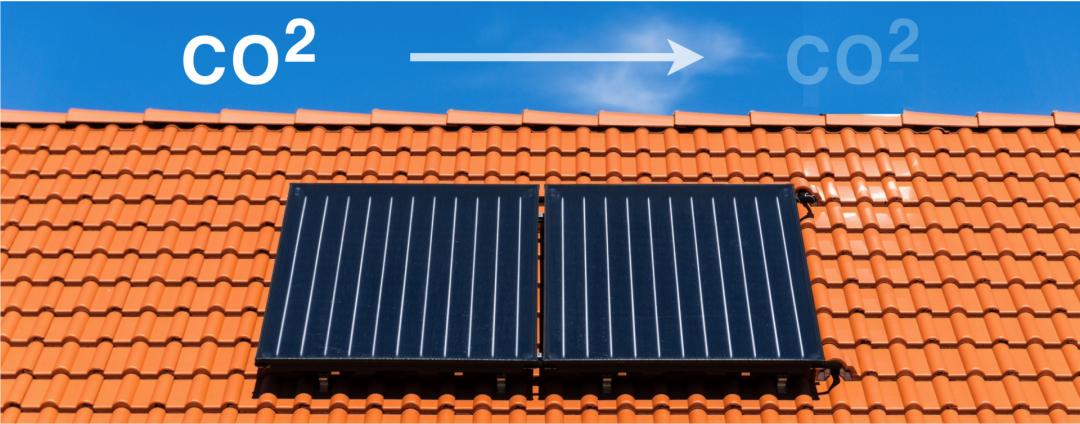Zwei Flachdachkollektoren auf einem roten Dach mit weißem Pfeil und CO2 Symbol, die die CO2 Reduktion der Solarthermie symbolisieren.