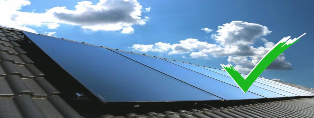 Eine blaue Solarthermie Anlage auf einem schwarzen Dach mit blauem Himmel und Wolken im Hintergrund. Ein grüner Haken symbolisiert die Vorteile.