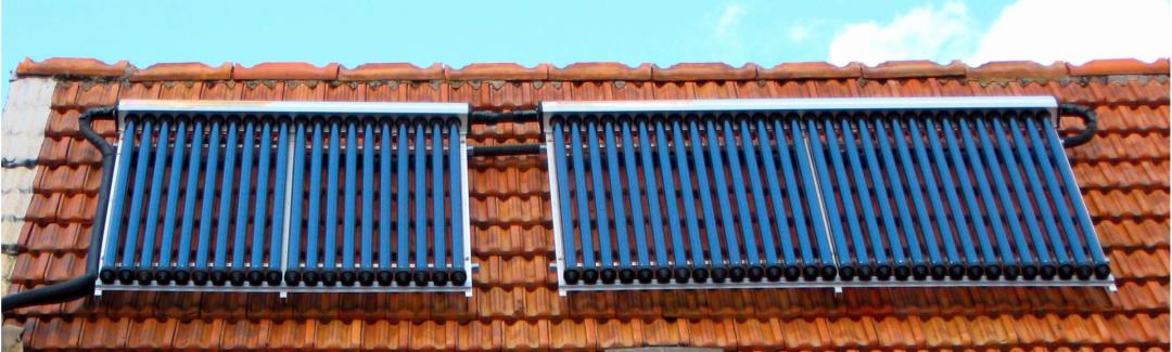 Röhrenkollektoren der Solarthermie auf einem roten Dach