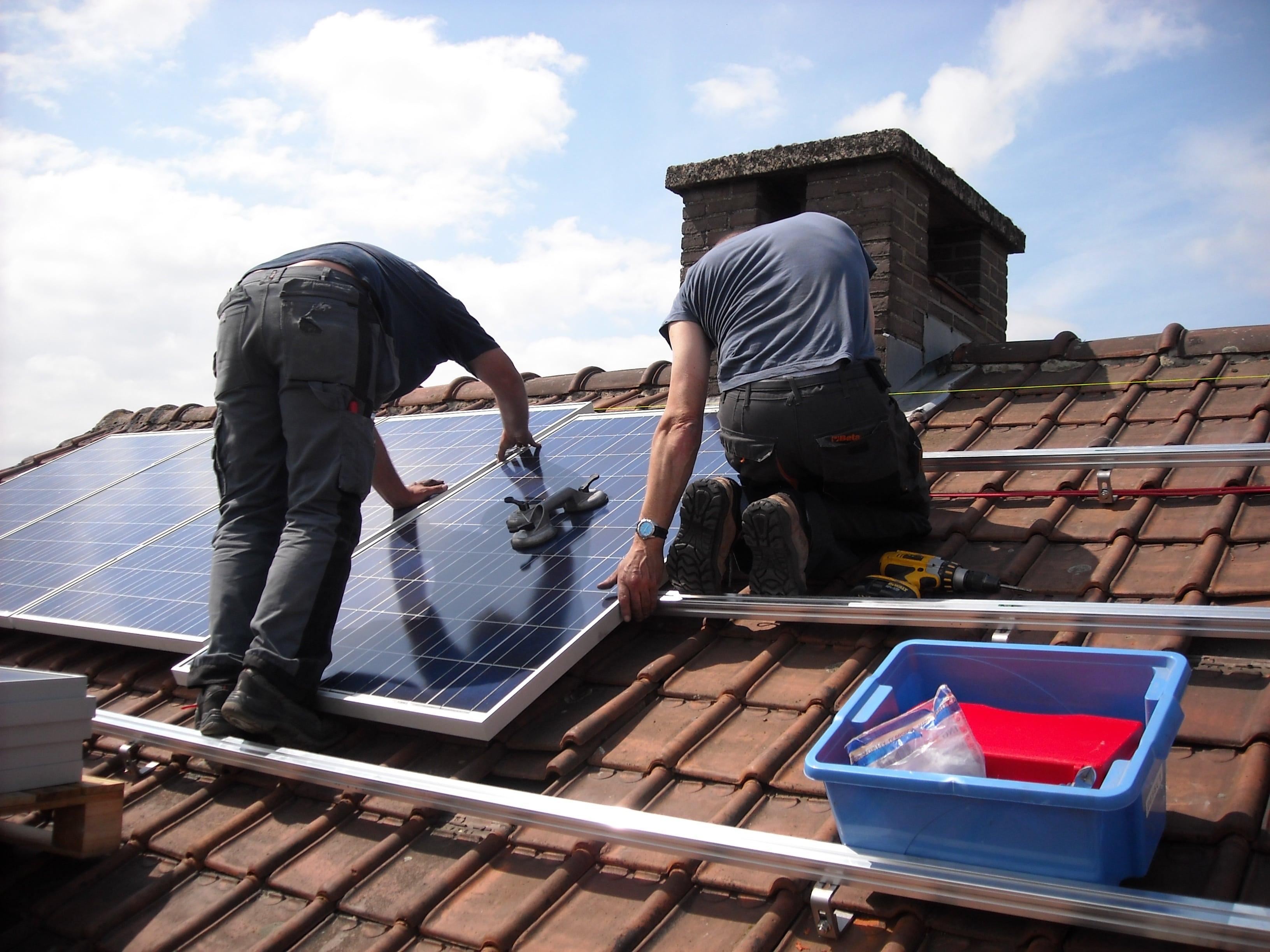 Zwei Handwerker auf einem Dach, die eine Solaranlage installieren