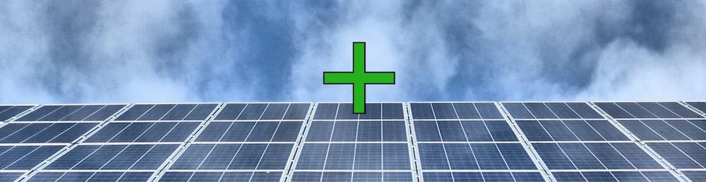 Die Vorteile einer Solaranlage mit einem grünen Plus auf einer grauen PV-Anlage symbolisiert