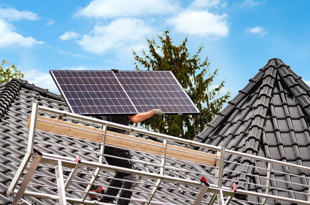 Zwei Handwerker auf einem schwarzen Dach, die Solarpanele installieren