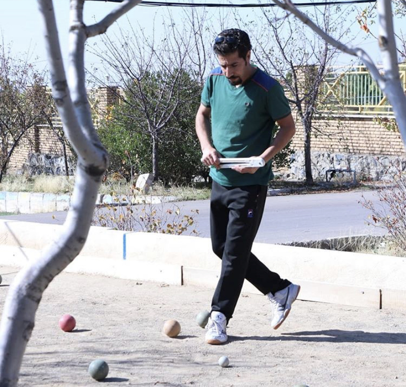 man standing on bocce ball court
