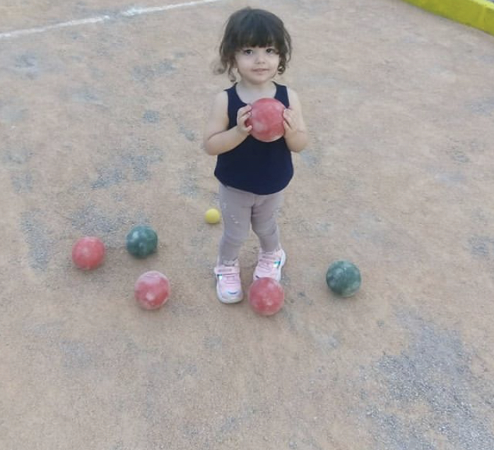 small child holding bocce ball