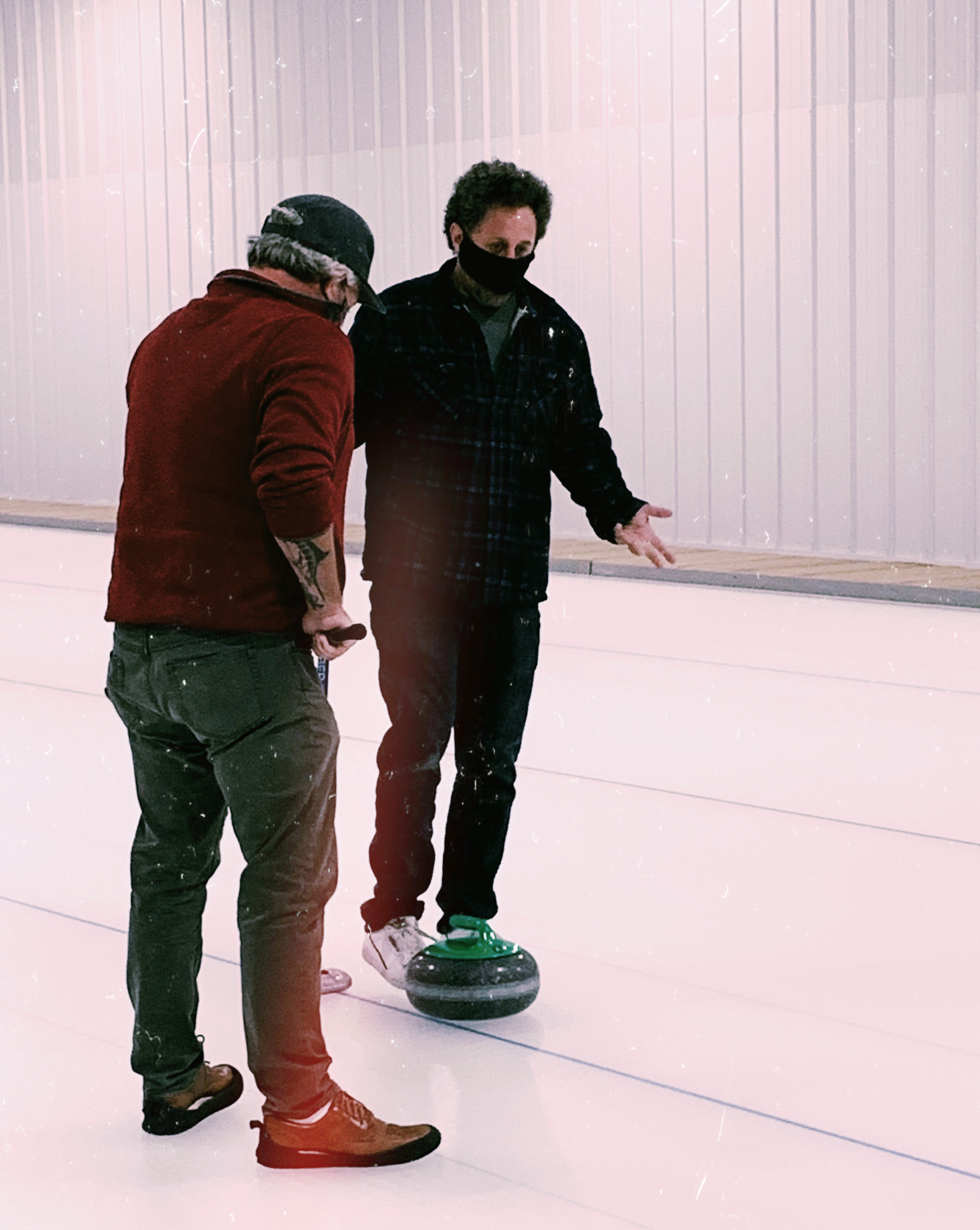 man teaching other man how to curl