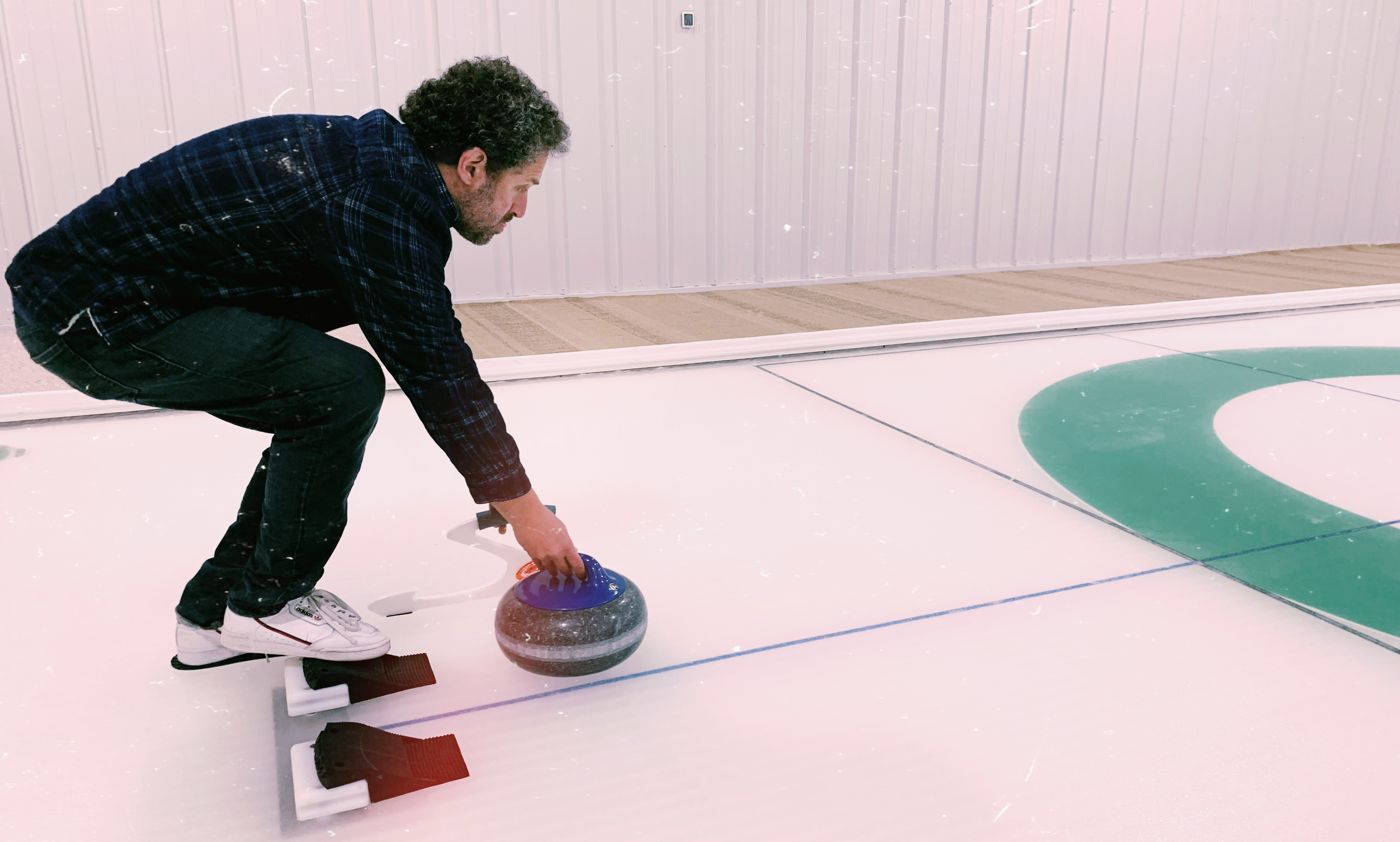 man curls stone down ice