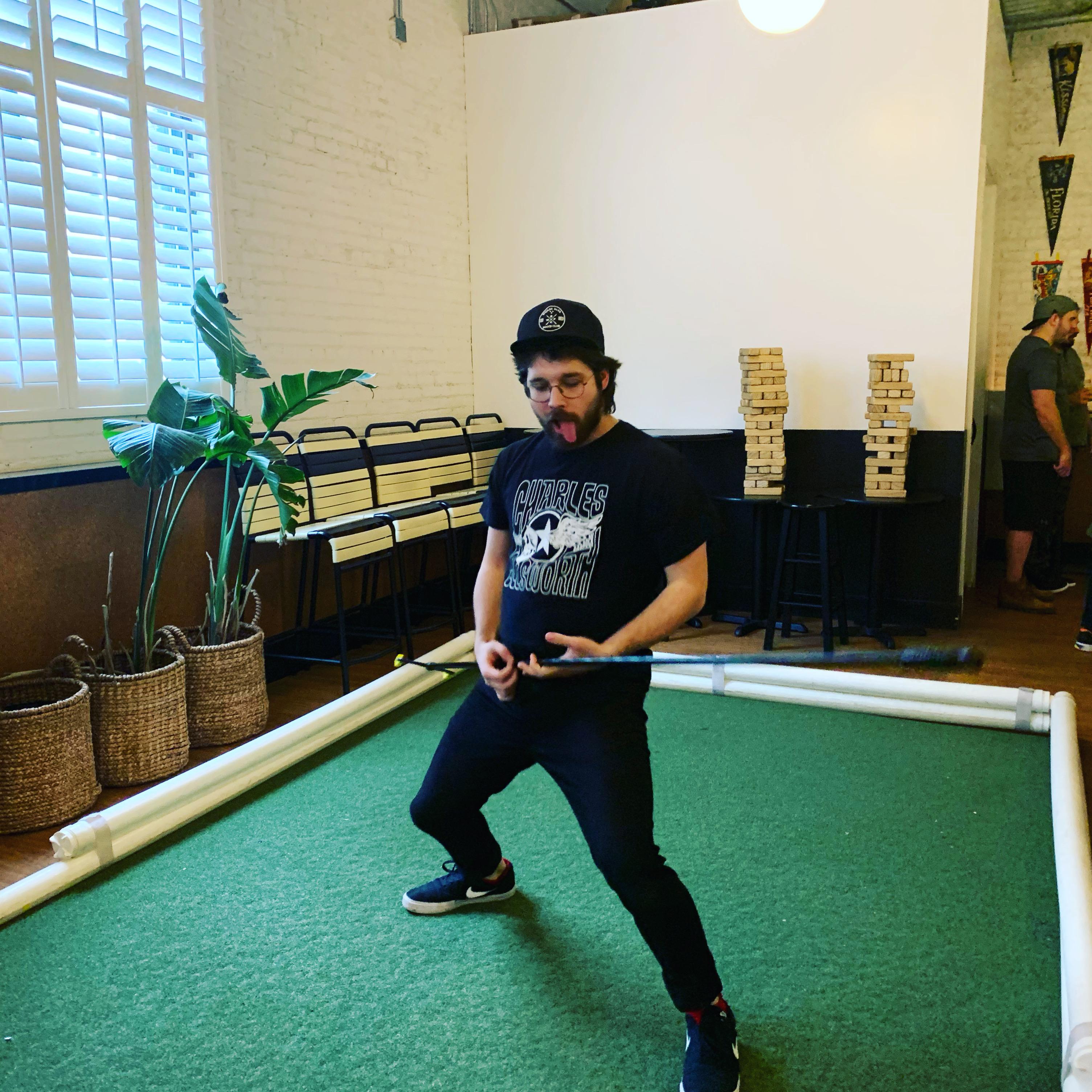 man plays air guitar with shuffleboard tang