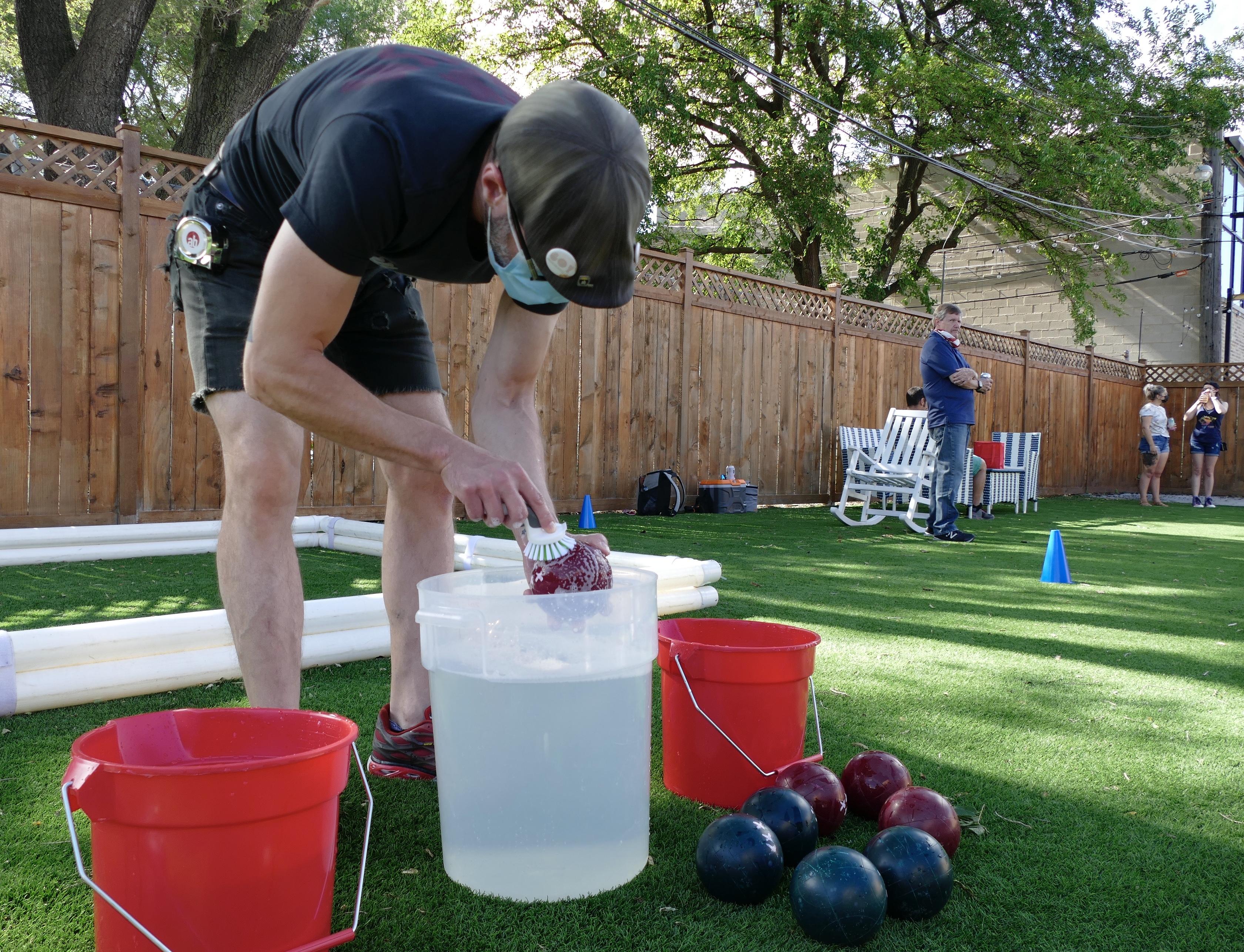 man washes bocce balls during pandemic