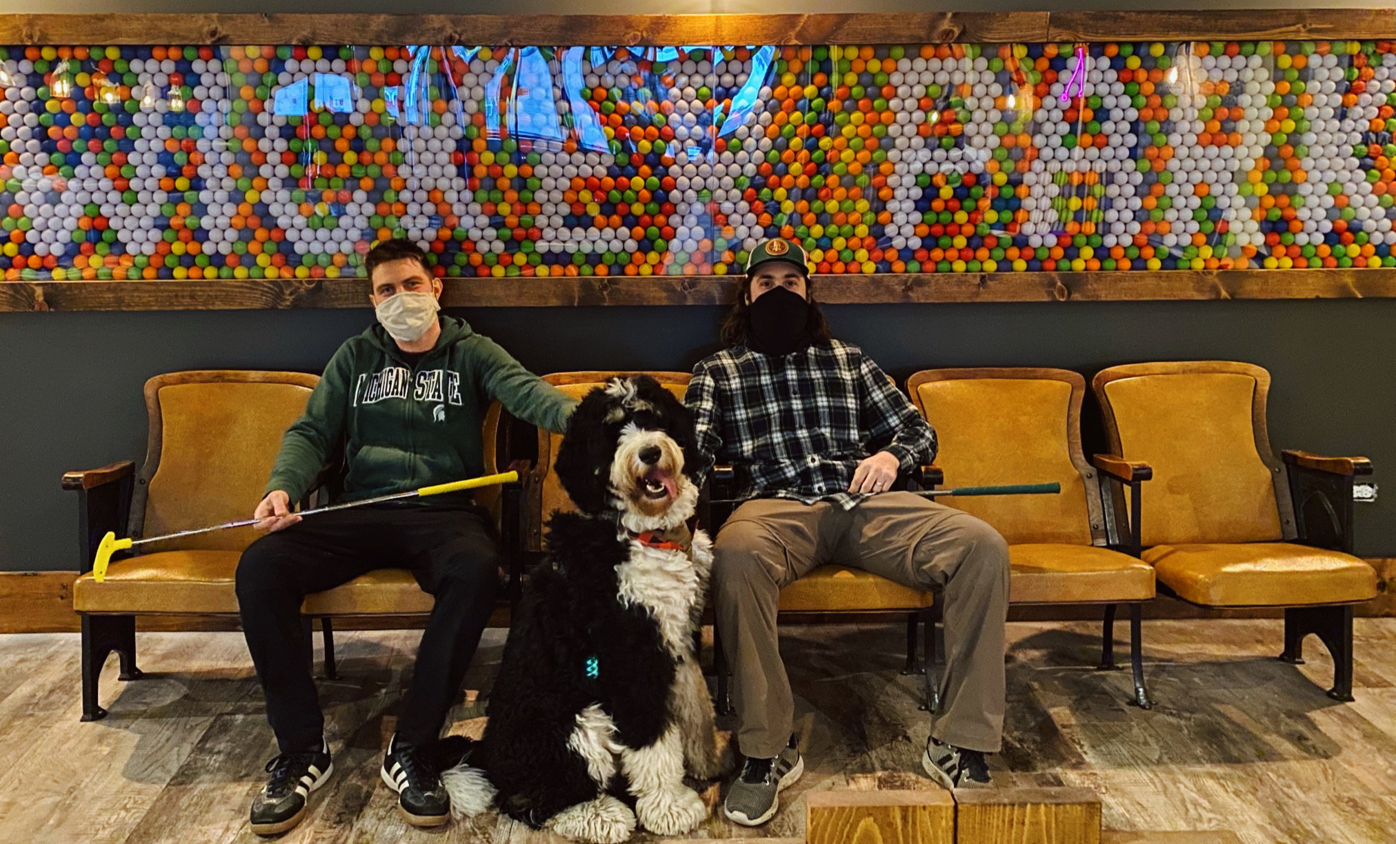 two guys and a dog sitting next to sign