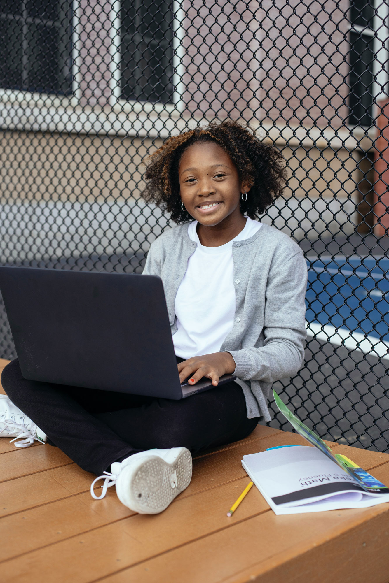 A cute teen smiling and holding a computer