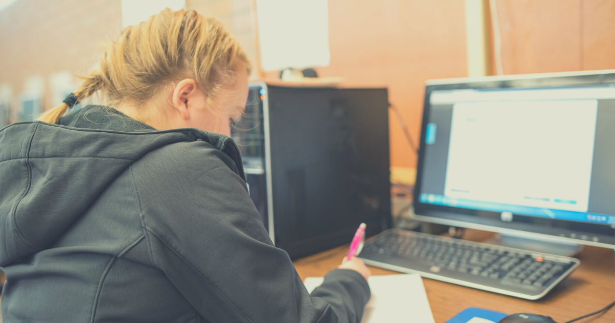 A student with a blonde French braid and black, hooded jacket uses EdReady on a computer lab desktop computer
