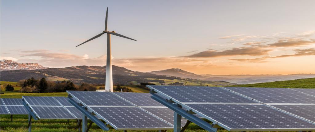 Ein Windkraftrad und Solaranlagen in der Natur, die unser Grünstrom symbolisieren