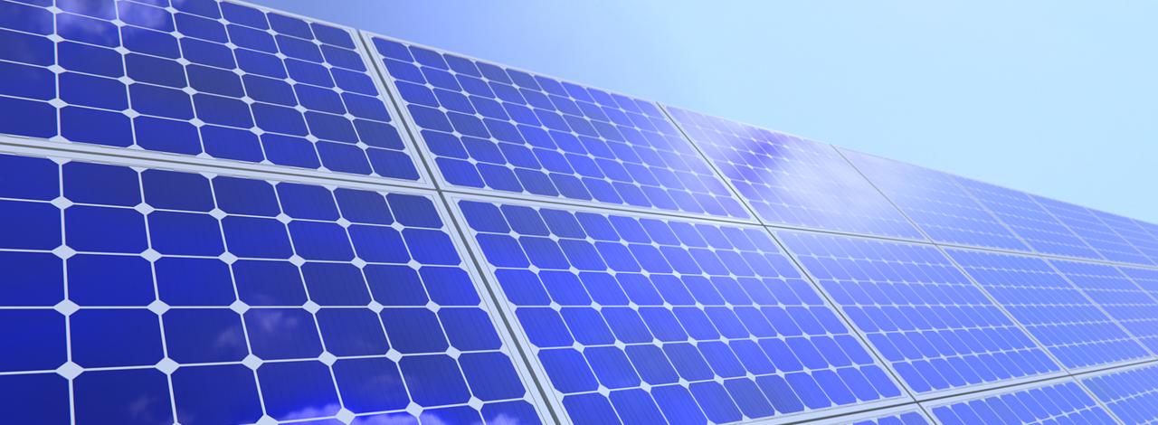 Solarzellen stehen im schrägen Winkel mit blauem Himmel im Hintergrund und symbolisieren die Solarenergie