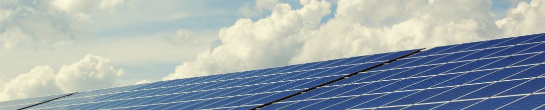 Viele Solarzellen nebeneinander bilden eine Fläche mit Wolken im Hintergrund