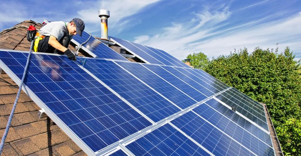 Man auf einem Dach bei der Montage einer Solarzelle