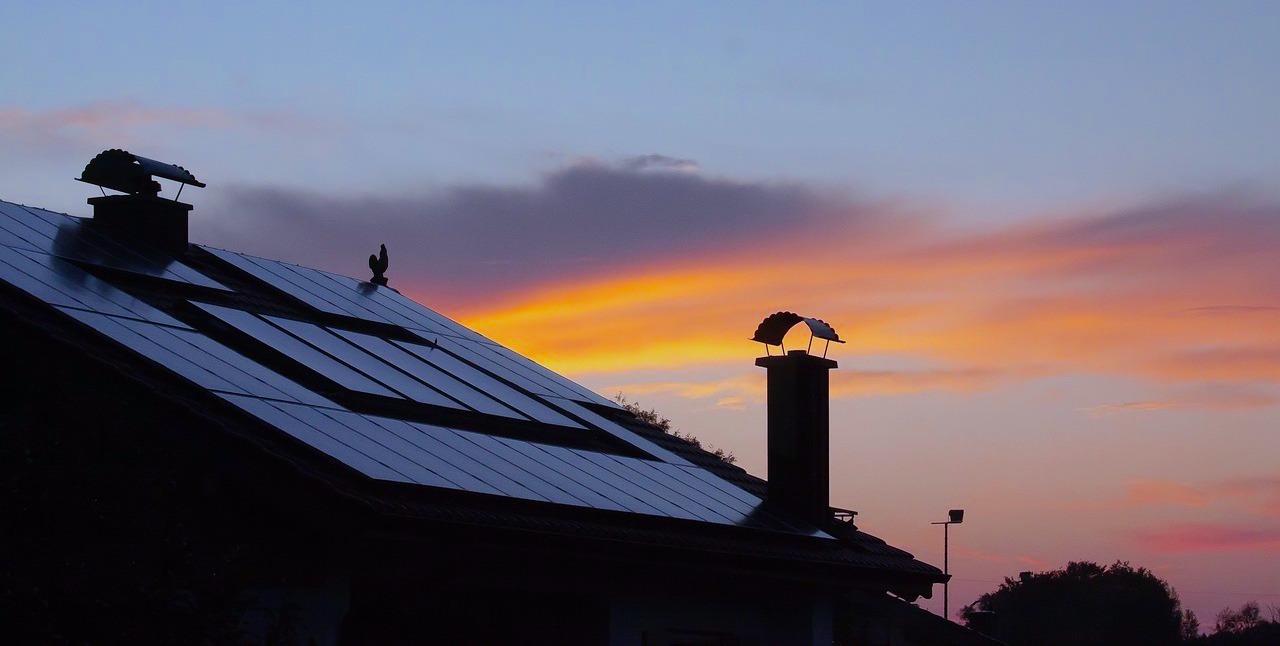 Solaranlage auf einem Dach mit Sonnenaufgang im Hintergrund