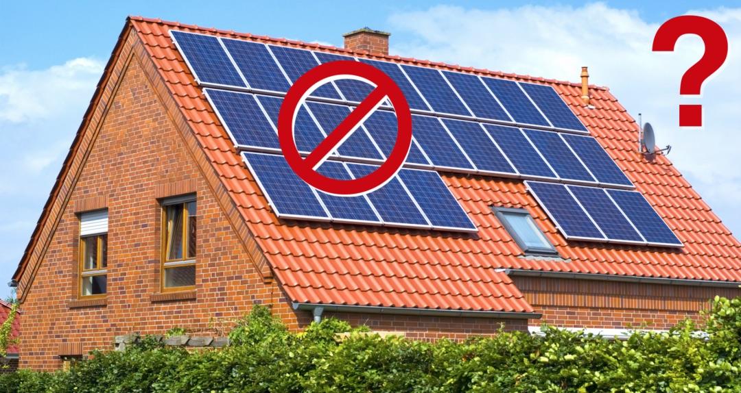 Rotes Haus mit Solaranlage auf dem Dach
