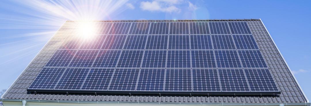 Eine Solaranlage auf einem grauen Dach mit blauem Himmel im Hintergrund, die das Solaranlage Mieten symbolisiert