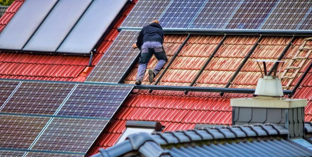 Ein Handwerker auf einem roten Dach, der eine Photovoltaikanlage installiert
