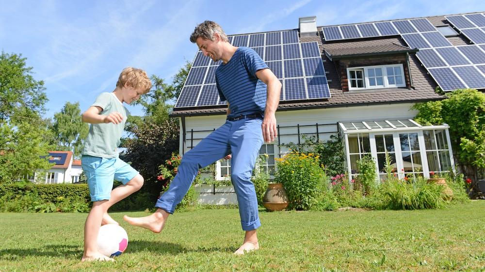 Vater und Sohn spielen Fußball auf einer Wiese vor einem Haus mit Solar.