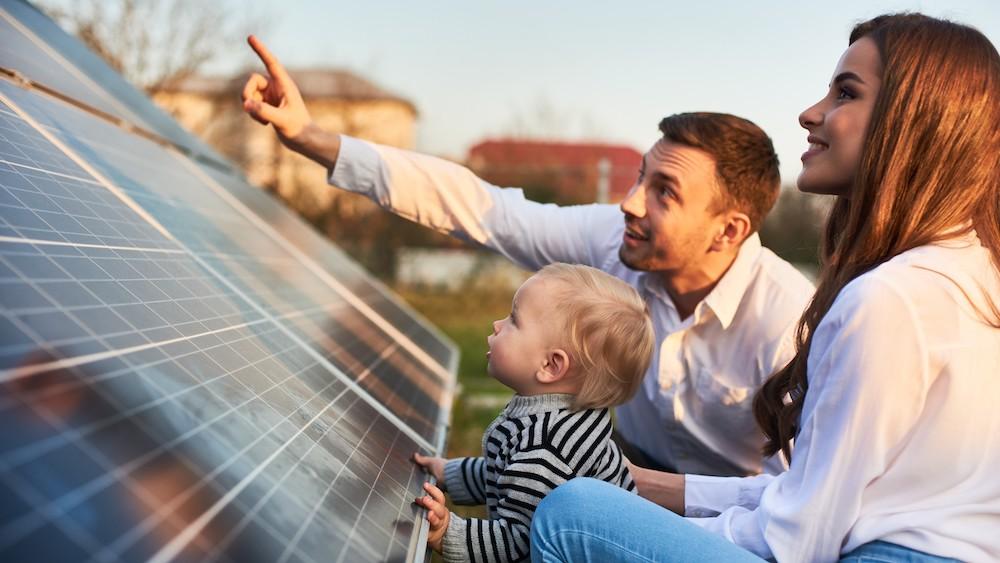 Familie mit Baby vor Solarmodulen.