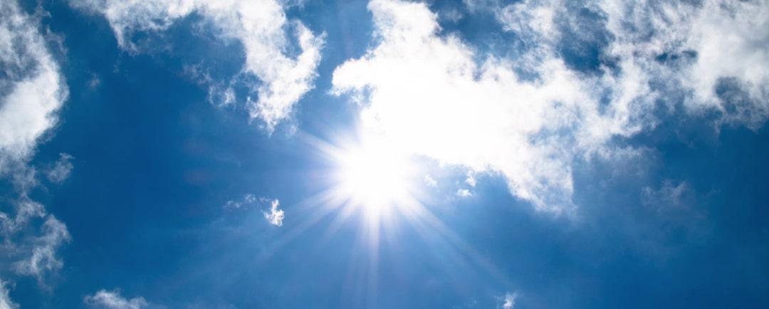 Solarenergie - Mittagssonne hoch am Himmel mit Wolken