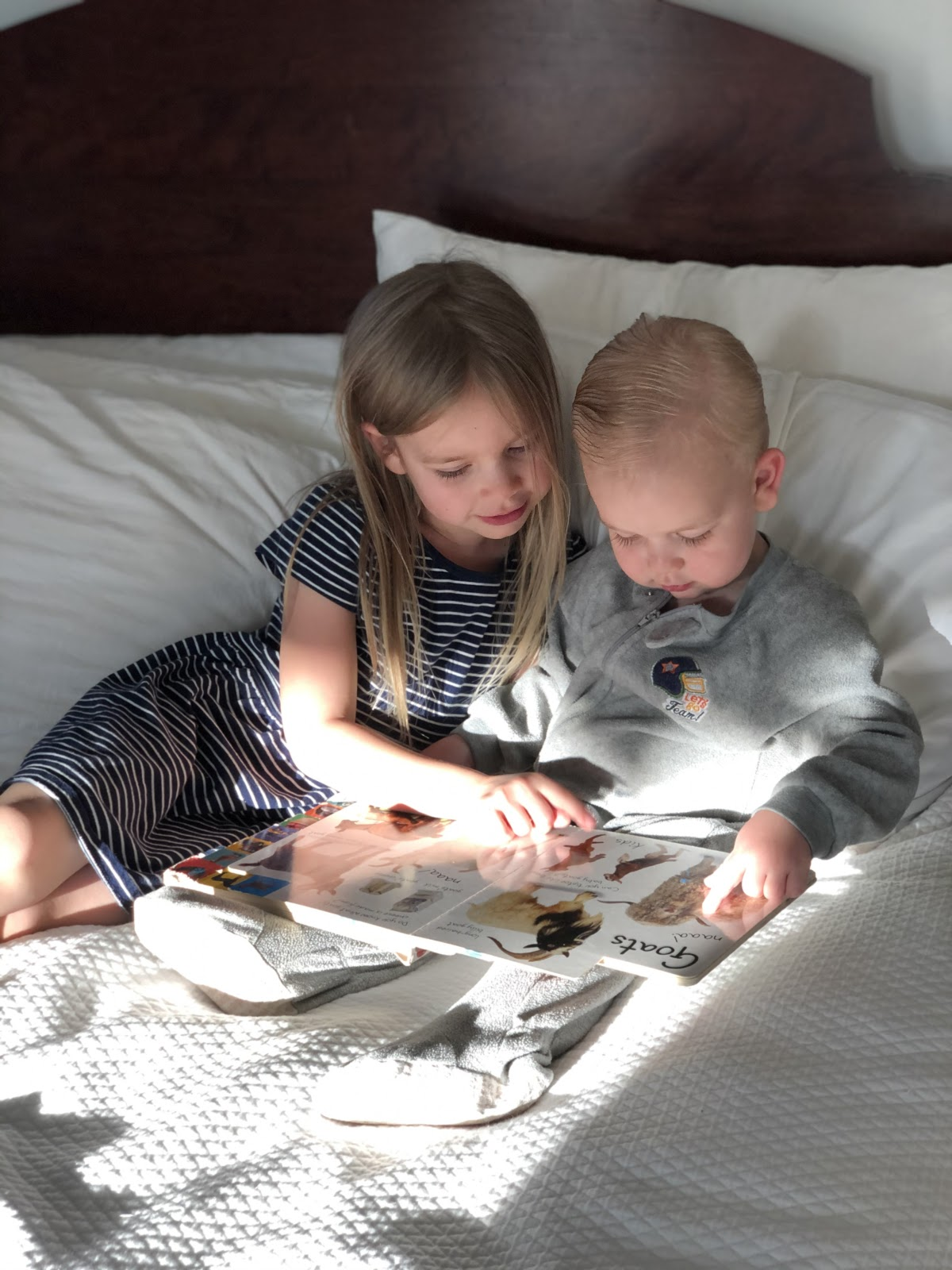two young children looking through a book
