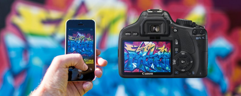 Smartphone and camera photographing graffiti wall